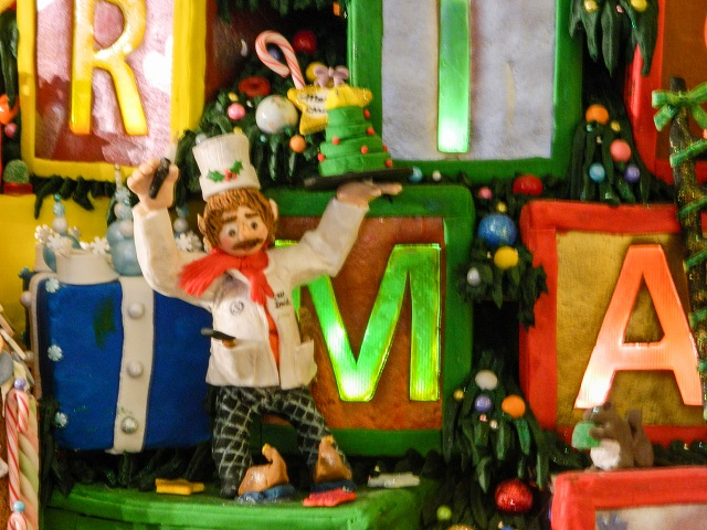 Detail of a baker on the O Christmas Tree gingerbread village, frosting a cake and wearing wooden shoes.