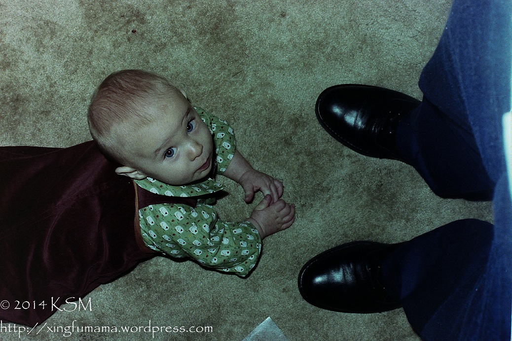 Baby facing his father's shoes looking up.