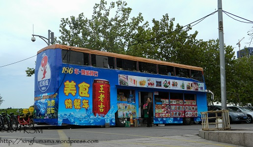 Qingdao waterfront: Double Decker Bus converted to a restaurant with a window selling drinks and snacks on the first floor and seating on the second floor.
