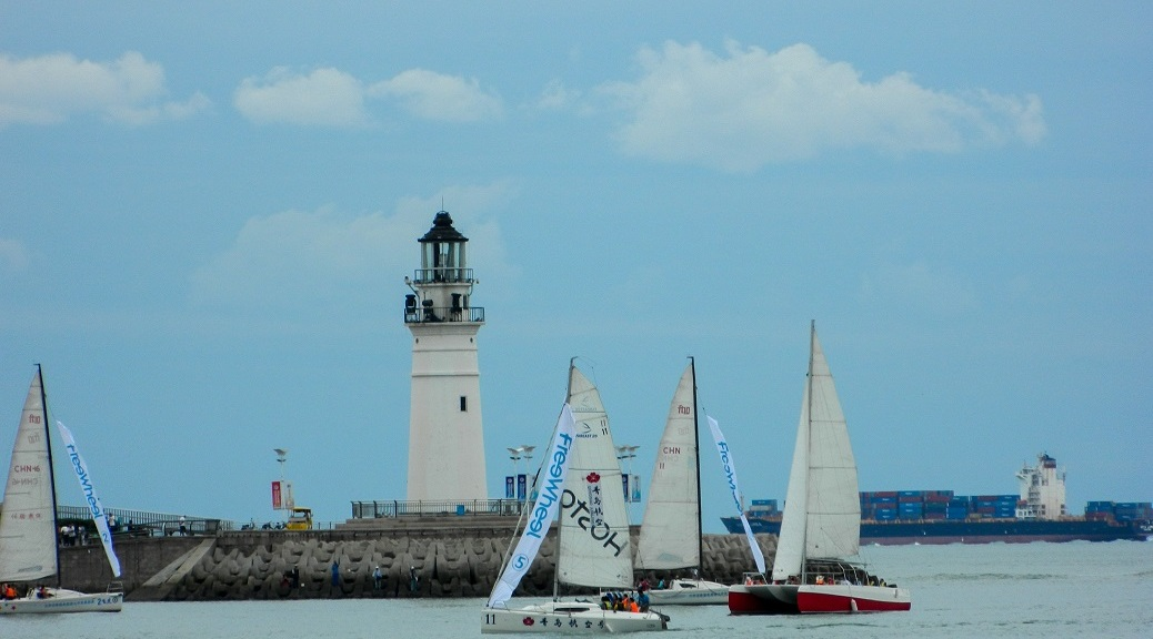 Light house and sailboats with a container vessel in the background.