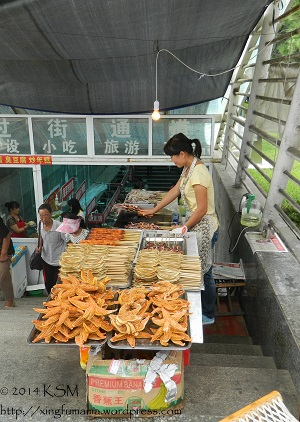 Vendor selling neatly displayed seafood on skewers and starfish.