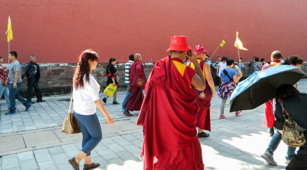 Buddhist monk walking through Forbidden City in Beijing, China. He is wearing a bright red toga and pork pie hat, orange sneakers and is talking on a cell phone.