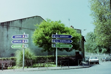 Road signs in Toulouse France, there are two sets of signs pointing in opposite directions with the same cities listed.