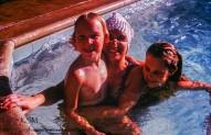 Mother with two children in swimming pool.