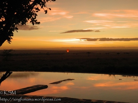 Dawn looking out over Masai Mara, an infinity pool in the foreground reflects the clouds and a hot air balloon is flaring.
