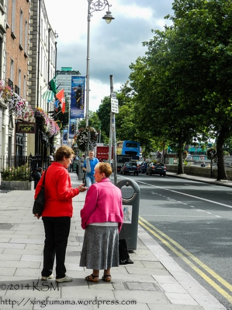 Two Irish women deep in conversation on a street in Dublin. They are wearing brightly colored coats.
