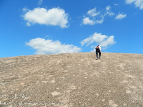 Hiker climbing Enchanted Rock in Texas toward a very blue sky with a few puffy white clouds.