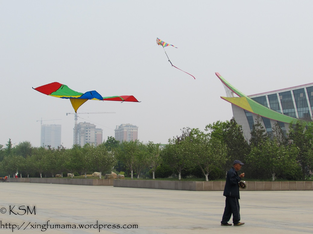Kites flying in the city square in Weifang China.
