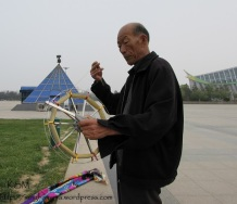 A Chinese man getting the reel of kite string ready.