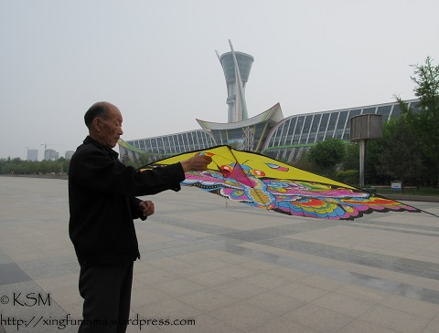 A Chinese man starting to fly his kite.