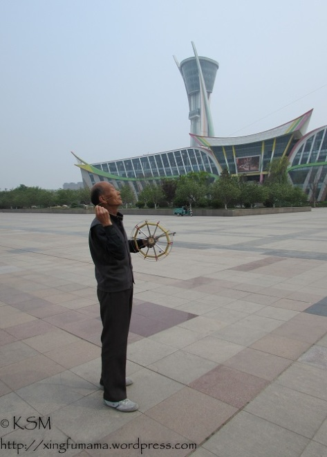 Chinese man holding the reel of kite string flying a kite.