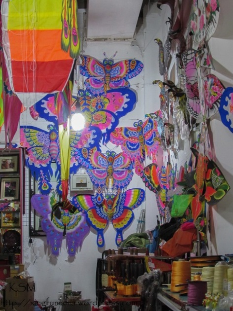 Several colorful butterfly kites hanging on a wall in a kite shop.