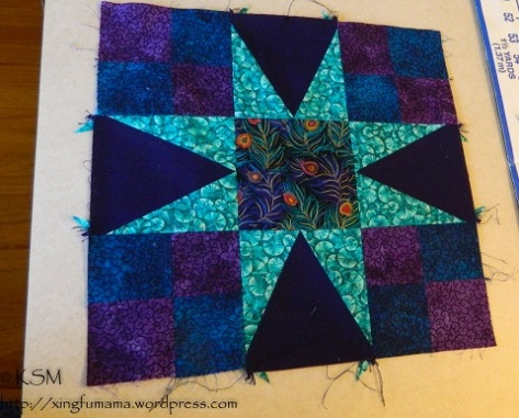 Quilt block in the 54-40 or fight pattern, shades of purple, blue and aqua.