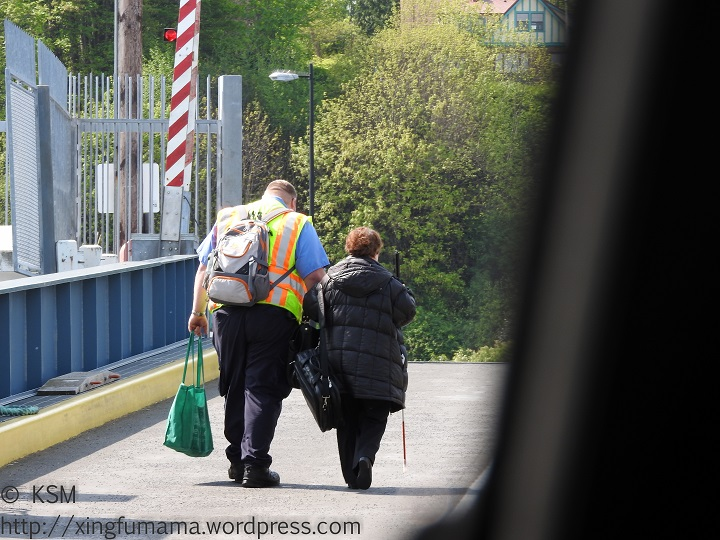 Ferry worker walking a blind woman up a ramp.