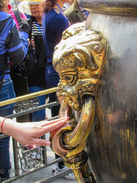 hadn touching the Lion handle of a water vat in the Forbidden City.