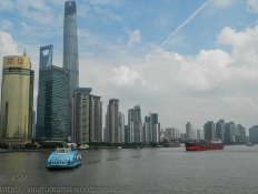 Huangpu River with Pudong skyline , a ferry and cargo boat.
