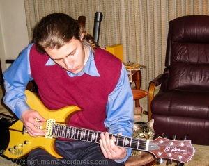 Young man playing a guitar.