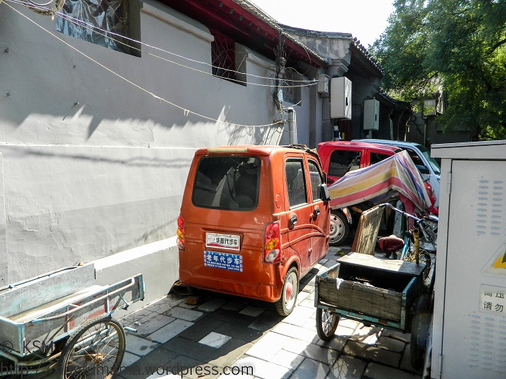 Assortment of vehicles parked on a sidewalk in Beijing.