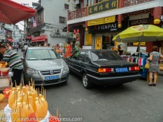 Street in an older part of town, shops and vendors narrow the street to where two cars can barely pass.