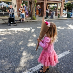 Little girl watching performers at the local farmer's market.