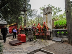 Confucius's simple grave stone peaks behind the more ornate one with the altar.