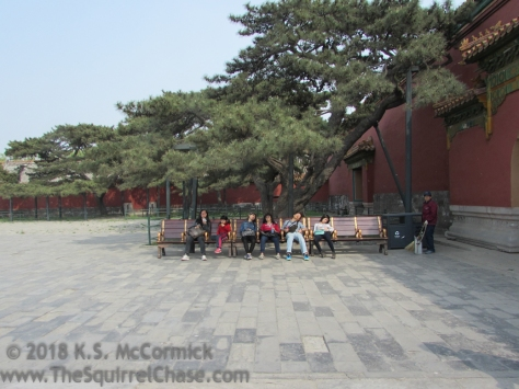 Tourists resting on a bench as a worker starts to sweep up. Forbidden City, Beijing, China.