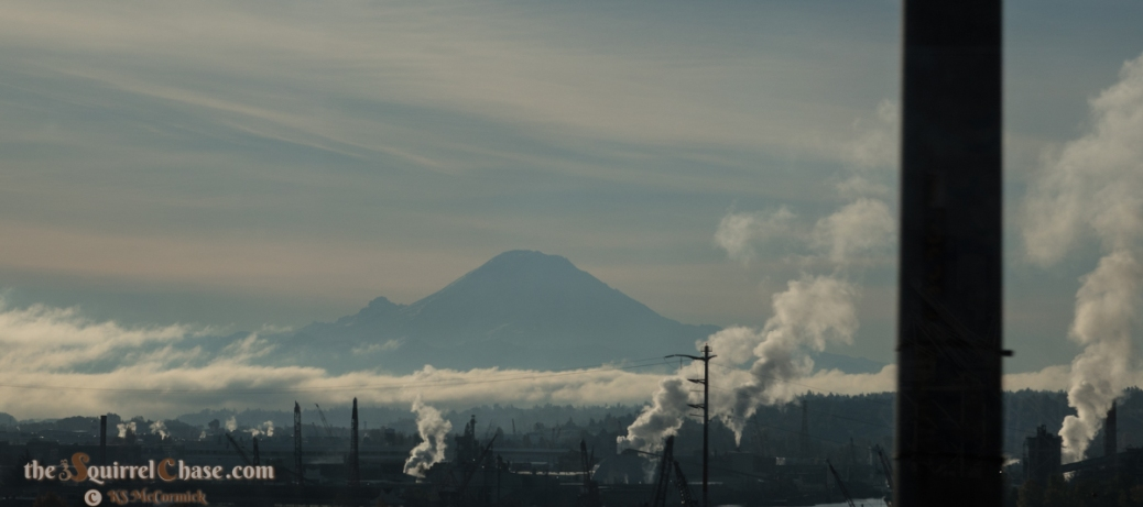 Mount Rainier's silhouette, low clouds, smoke stacks.