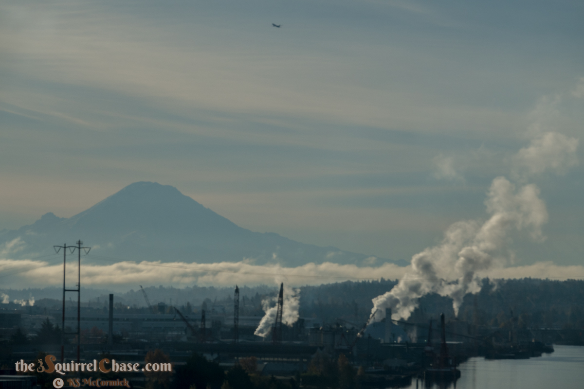 Mount Rainier's silhouette, low clouds and smoke stacks.