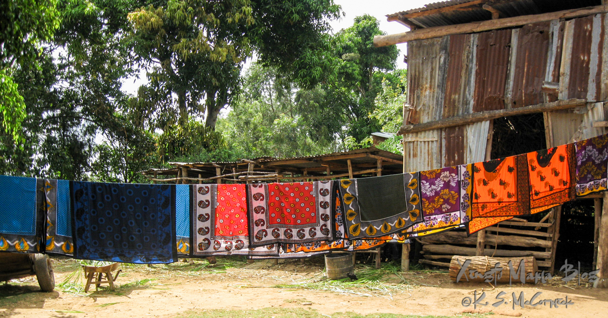 Brightly colored khanga (lesos) on a laundry line in Mulundi Village, Kitui District, Kenya.