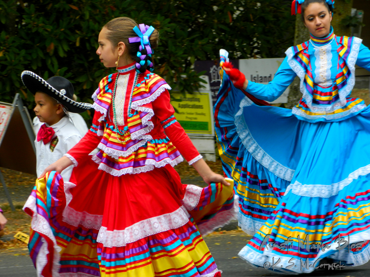 Mexican dance group wearing brightly colored dresses in a parade in West Seattle.