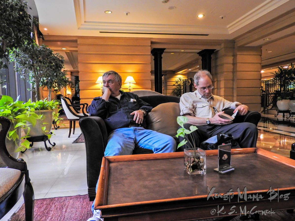 Two men waiting in a hotel lobby.