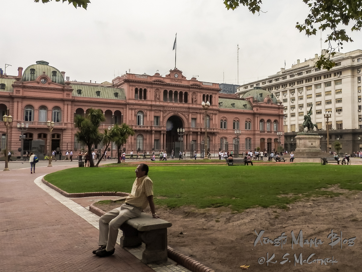 Man on a park bench beside the Casa Rosa in Buenos Aires.