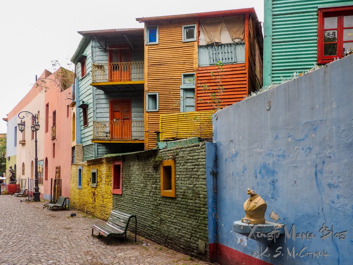 Benches along a cobblestone street of colorful buildings in the La Boca district of Buenos Aires.