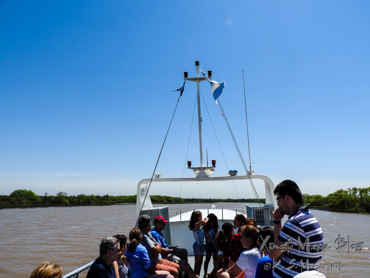 People sitting in the open air top deck of a tour boat in the Parana Delta Argentina.