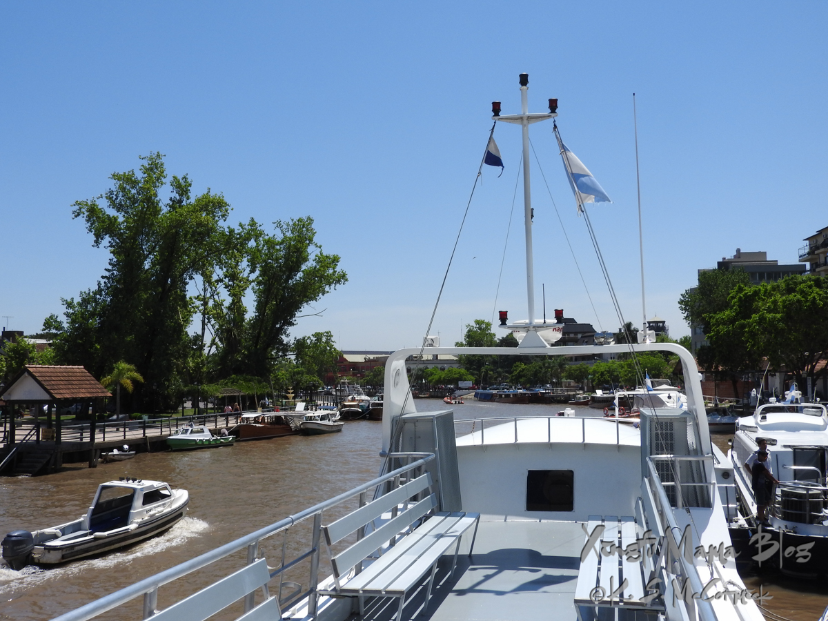 Bench seats, empty now, on the open deck of the tour boat, docked in Tigre.