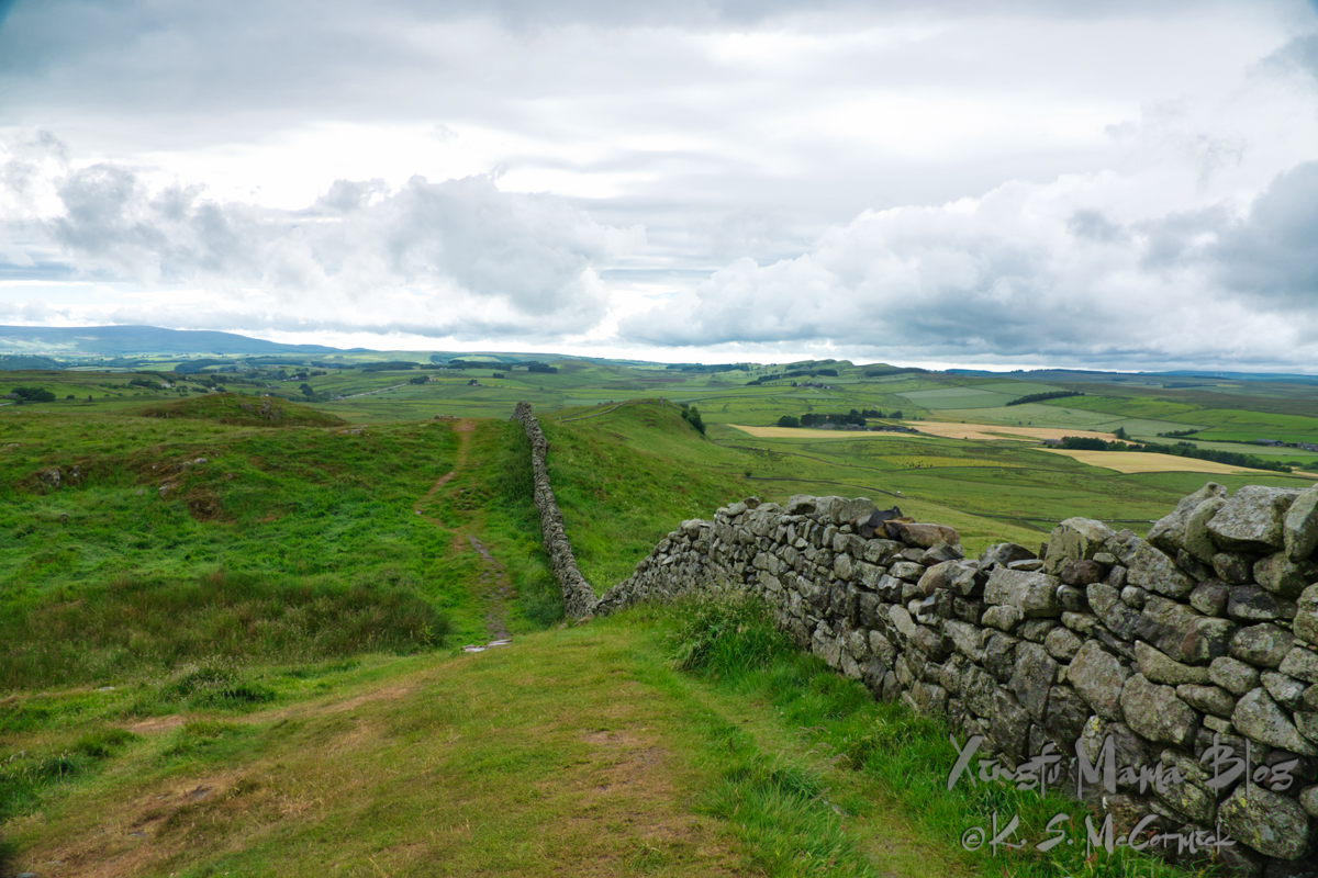 Stone wall that is the remains of Hadrian's Wall goes straight up and down hill in the Northumbria countryside.