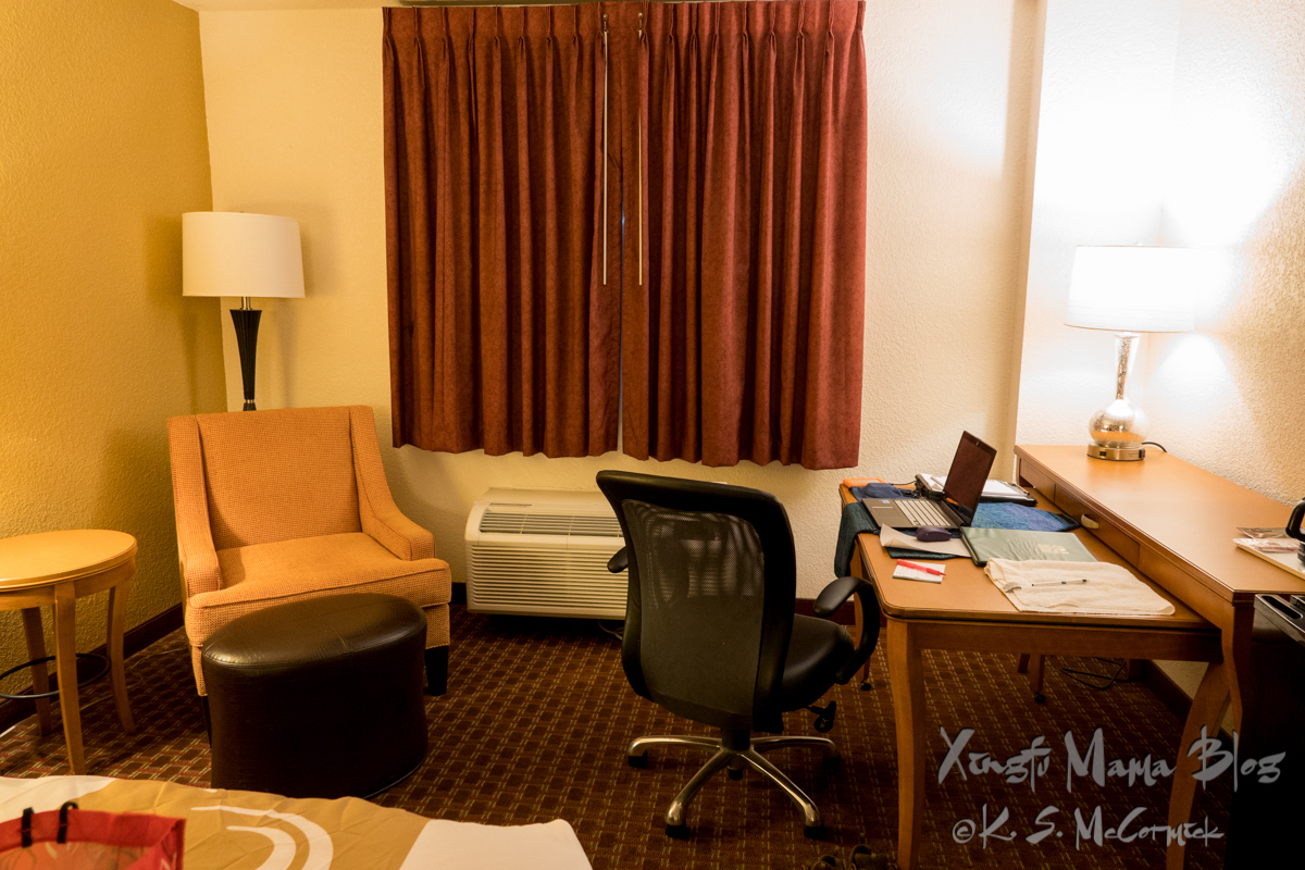Computer desk and chair and easy chair in a hotel room.