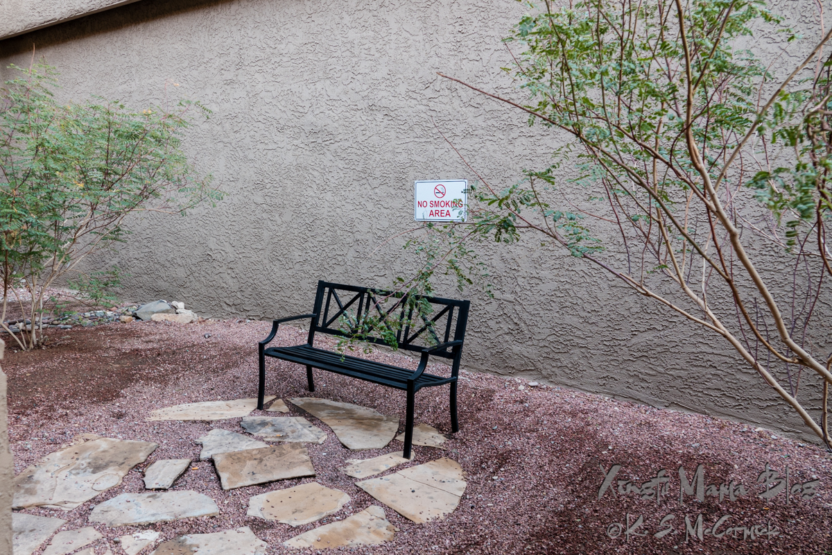 Black outdoor bench with a sign that says no smoking area.
