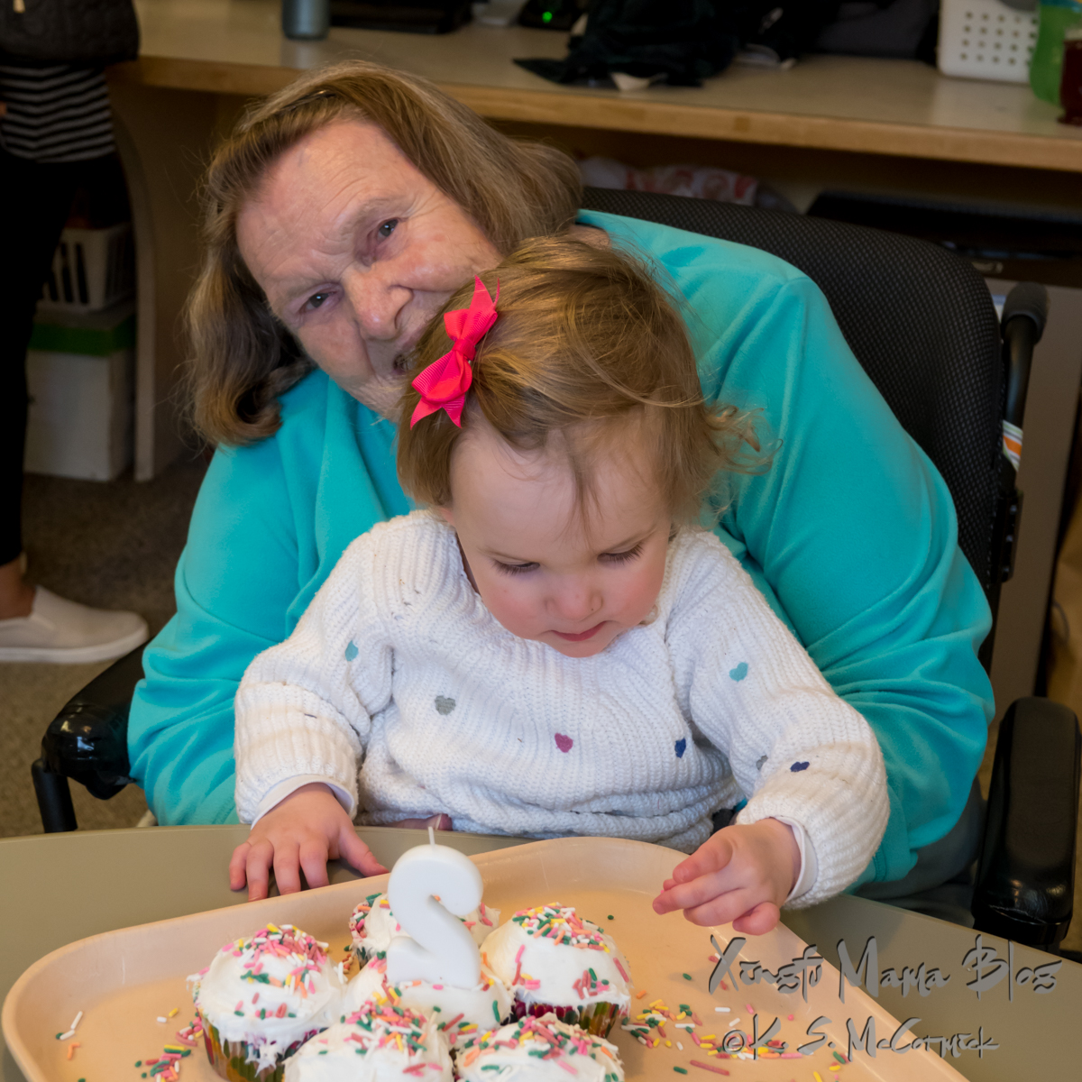 Woman in wheelchair holding a toddler who is playing with sprinkles from her birthday cupcakes.