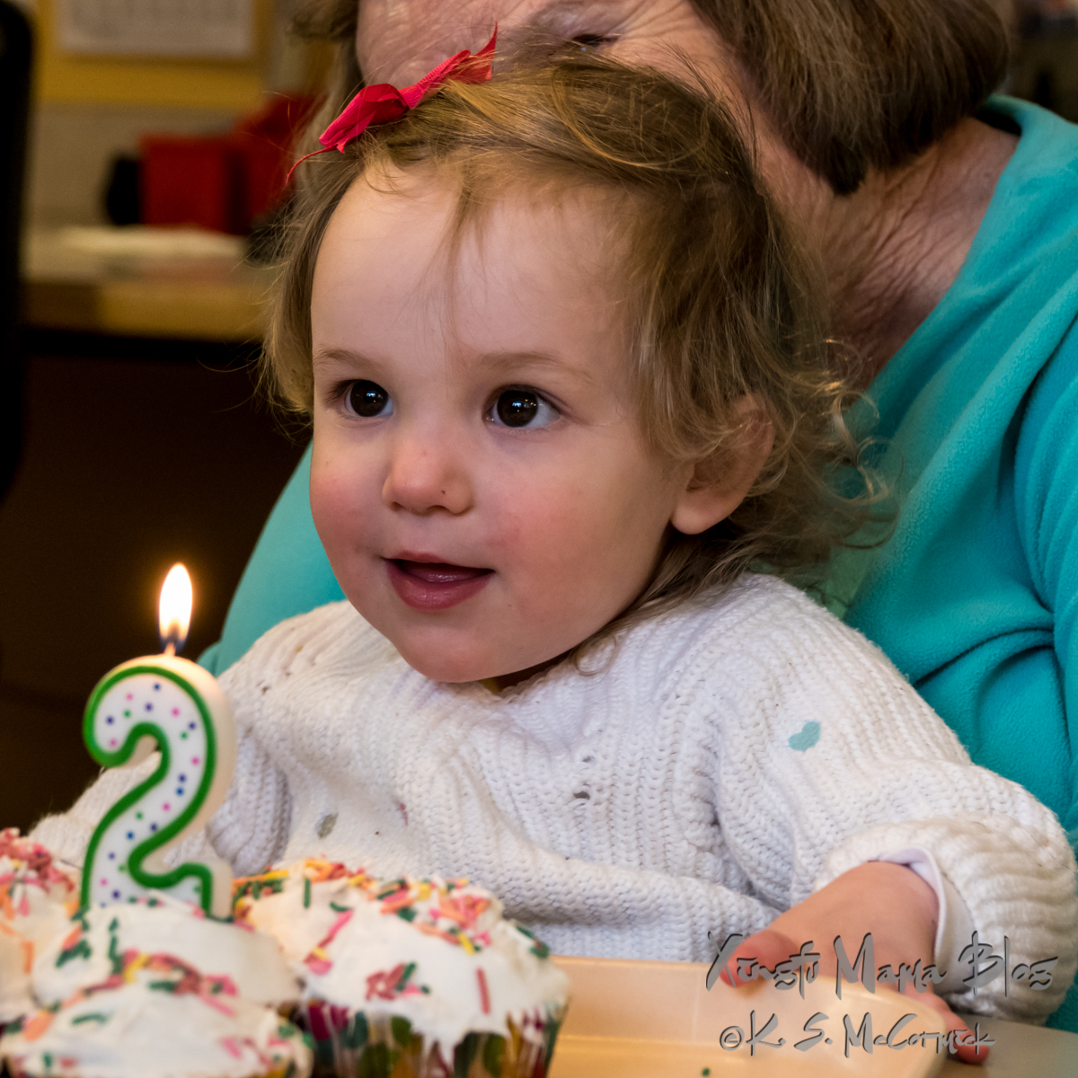 Toddler with birthday candle and cupcakes.