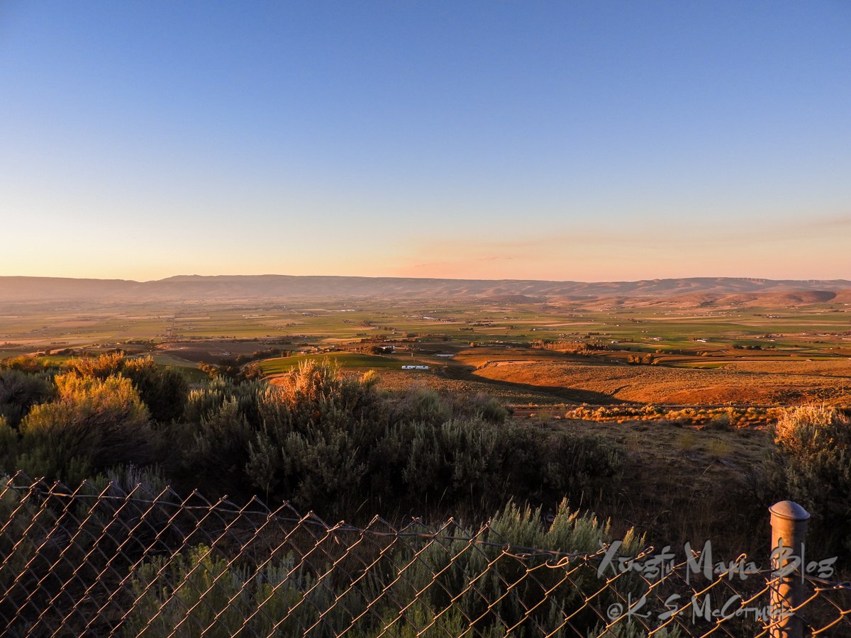 Chain link fence in the foreground of a landscape of rolling hills at sundown.