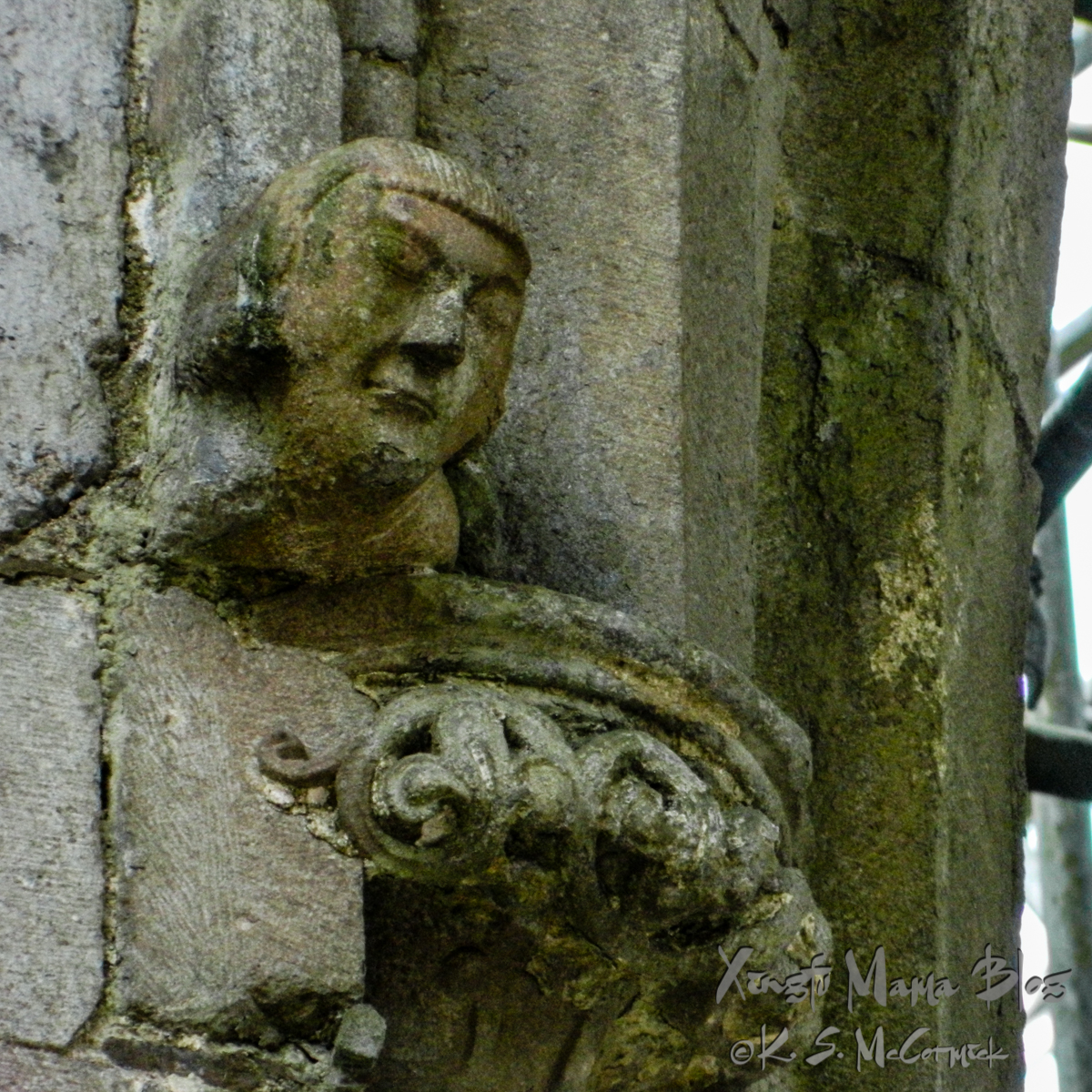The carved head of an important church man looks down on those walking through St. Patrick's Cathedral at the Rock of Cashel in Ireland.