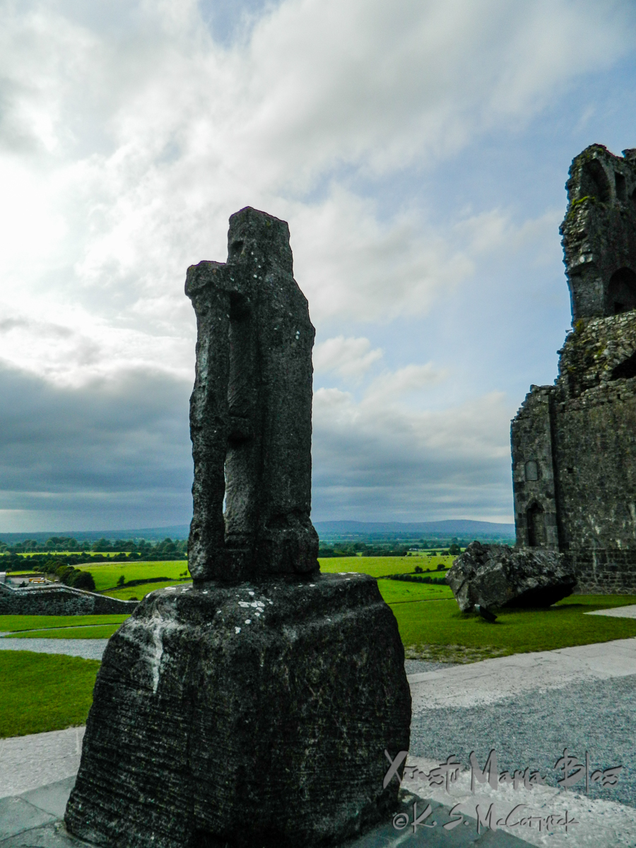St. Patrick's Cross at the Rock of Cashel. A stone cross with Irish countryside and a bit of weather in the background.