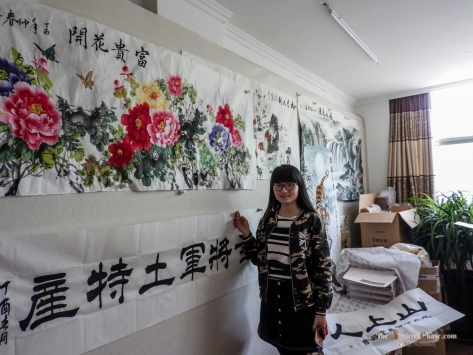 Young woman shows some of her Chinese painting and calligraphy.