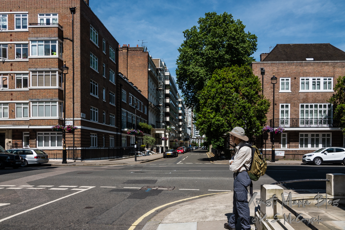 A man in a hat and backpack looking at cars passing on a London Street.