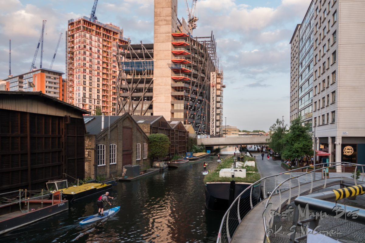 Paddleboarders paddling past old warehouses and canal boats in the Paddington Basin in London.