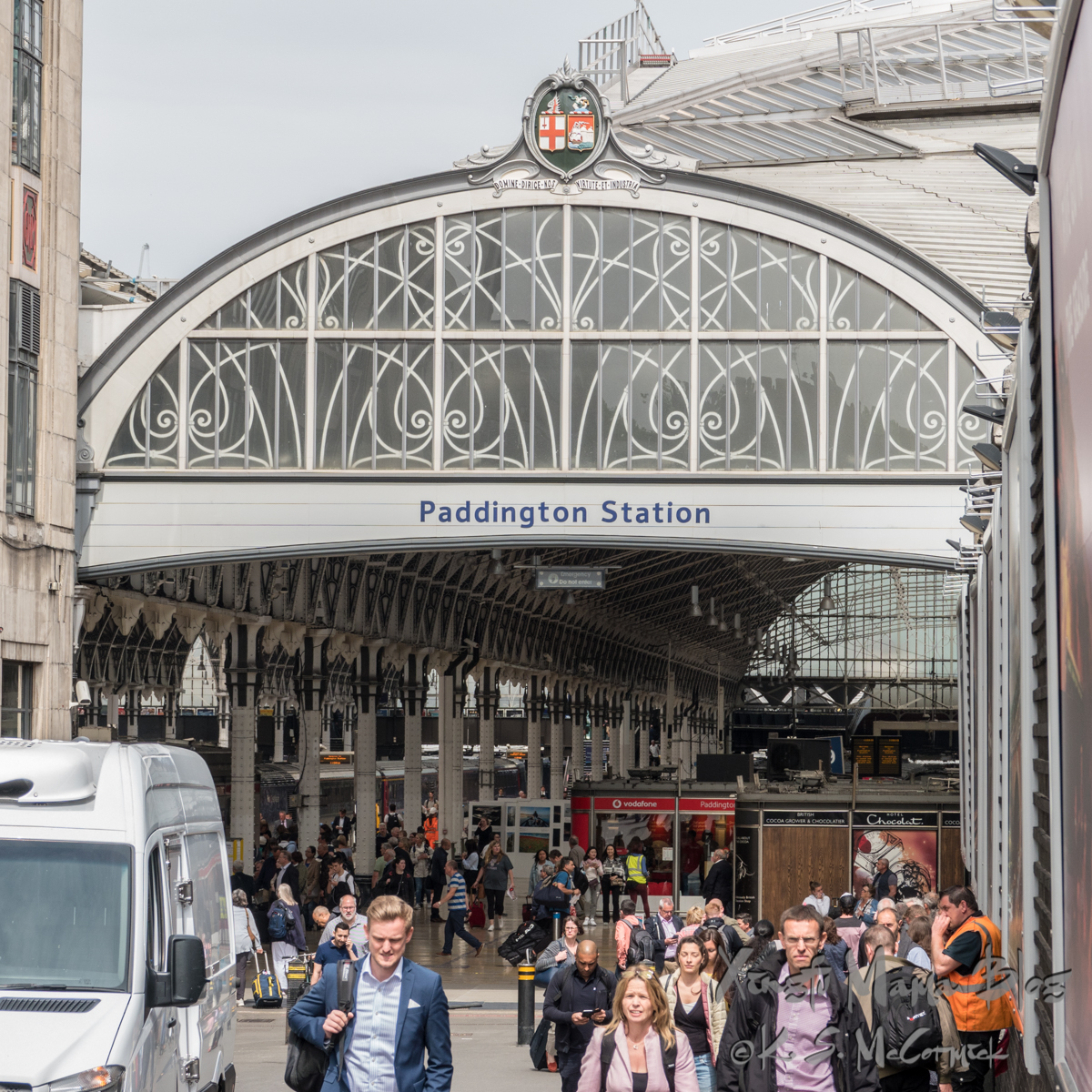 People walking out from under the ornate arch at the entrance to Paddington Station in London.