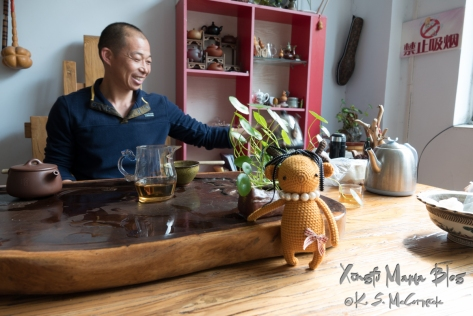 Amie Lu, a toy deer, leaning against a tea table with a chinese man in the background.