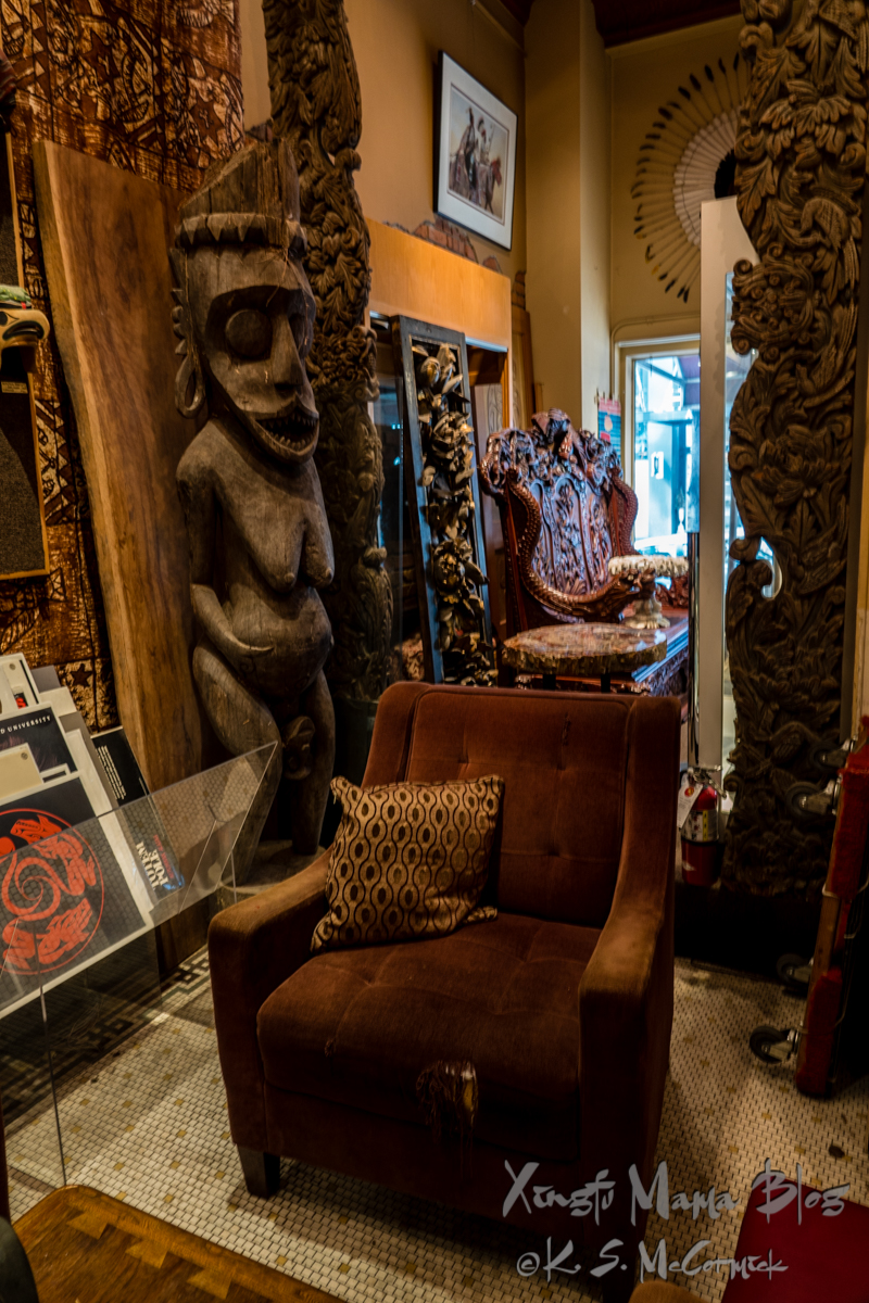 Brown velour chair with some fraying in the foreground, carvings from Asia and the Pacific rim behind it.