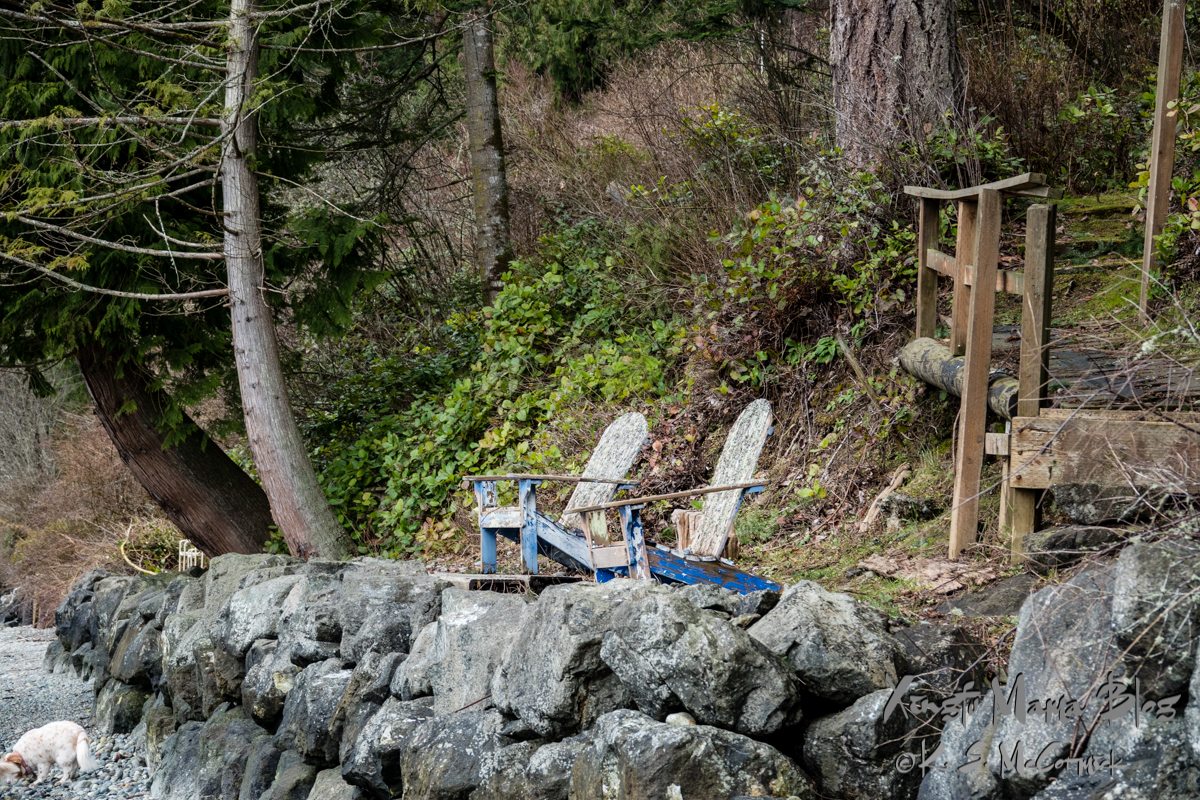 Two weathered blue Adirondack chairs on a stone bulkhead.